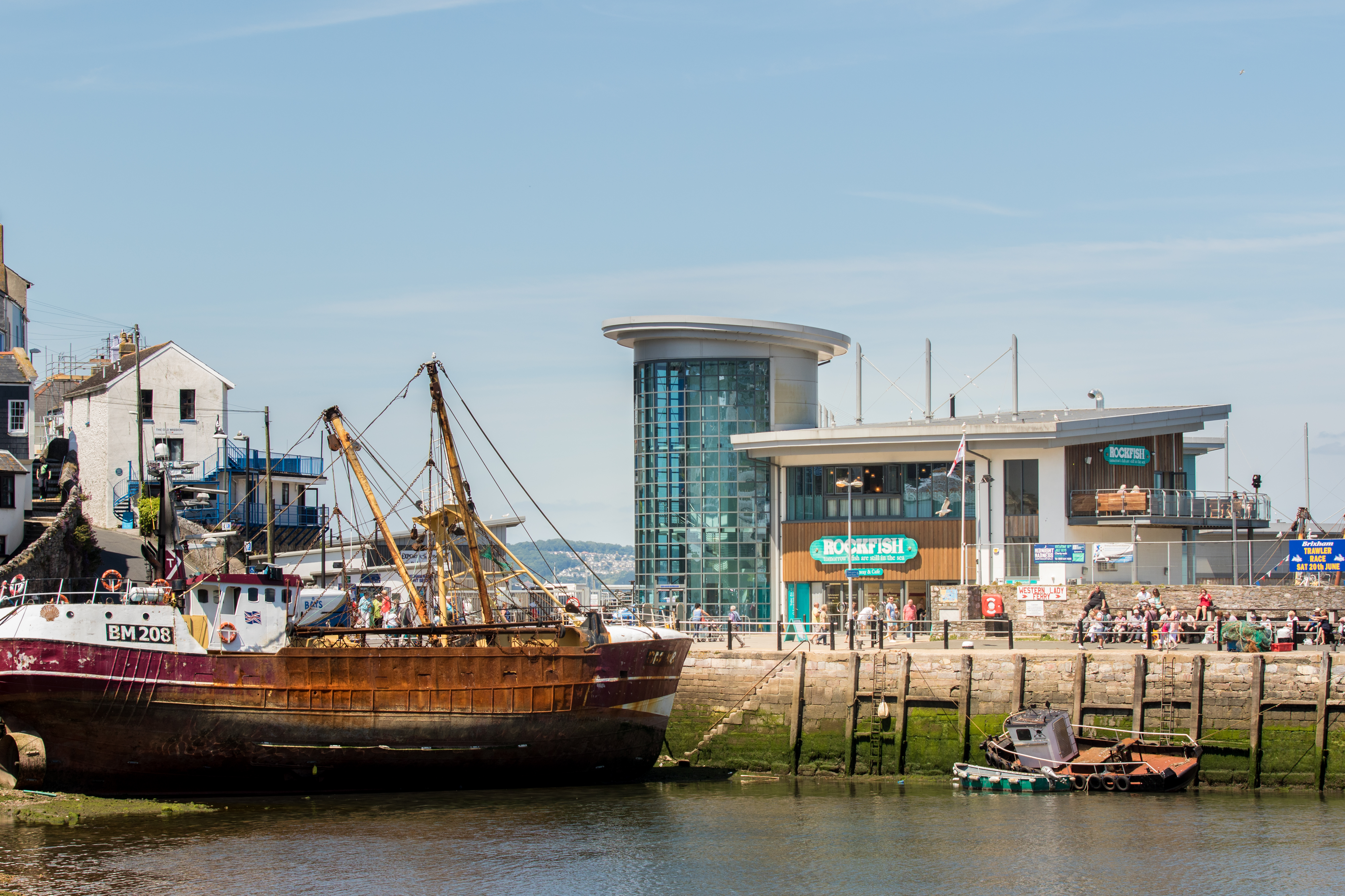 A photo of Rockfish Brixham building on a lovely day with low tide, there is a sea fishing boat in the photo.